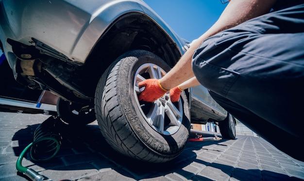 El mecánico de automóviles profesional reemplaza el neumático en la rueda.