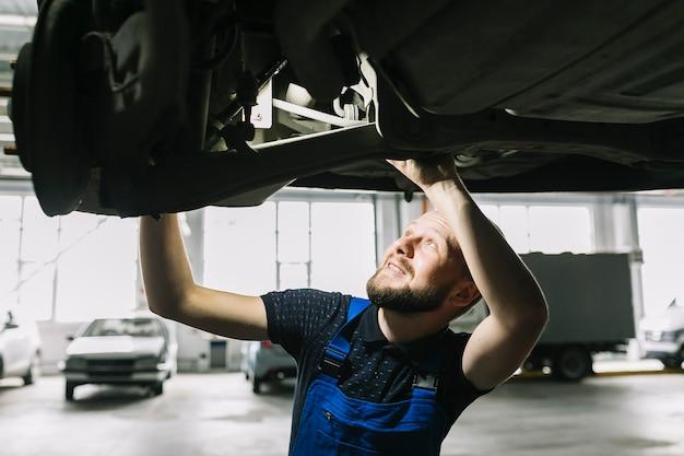 Mecánico de automóviles que mira el avellanador del coche