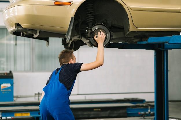Mecánico de automóviles que sostiene el avellanador en el coche