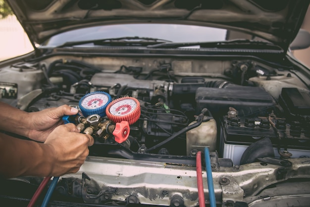 Mecánico de automóviles que utiliza la herramienta de equipo de medición para el llenado de los acondicionadores de aire de automóviles viejos.