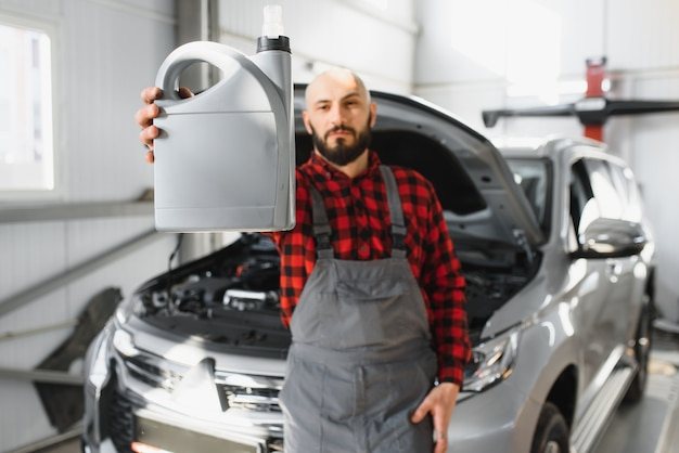 Mecánico de automóviles reemplazando y vertiendo aceite nuevo en el motor del automóvil