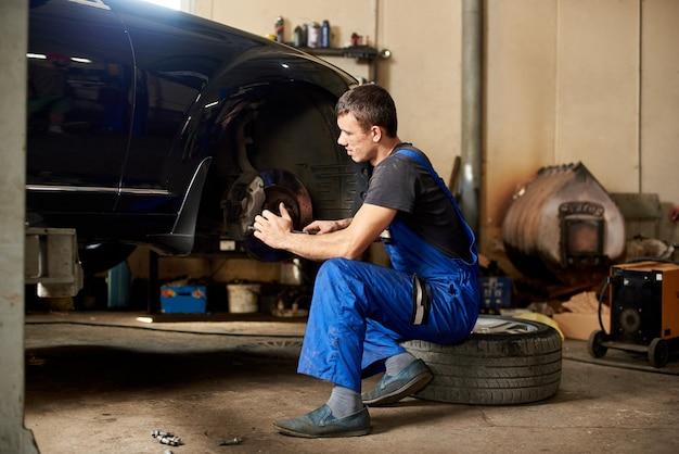 Mecánico de automóviles repara el coche en el garaje.