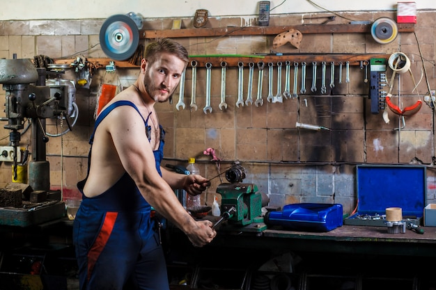 El mecánico de automóviles repara un detalle sujeto a un tornillo de banco.