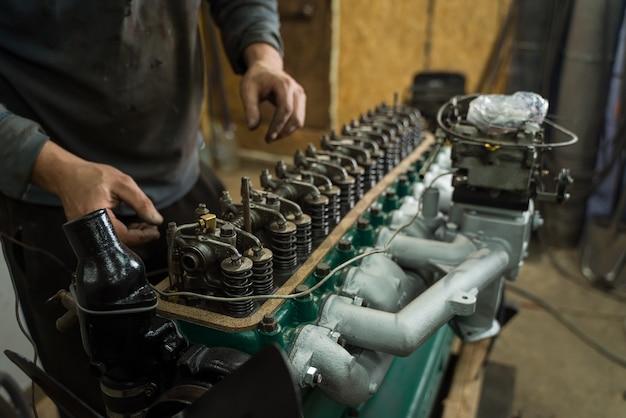 Mecánico de automóviles reparando un motor. mecánico que trabaja en el motor del coche. taller mecánico.