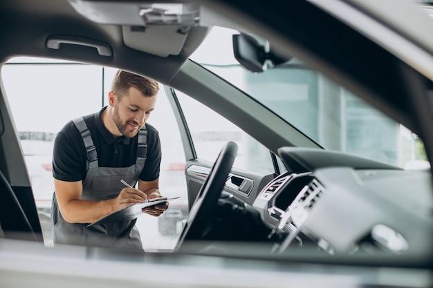 Mecánico de automóviles revisando un automóvil en un servicio de automóviles