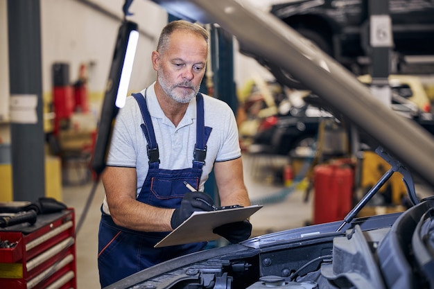 Mecánico de automóviles serio tomando notas en la estación de servicio de reparación de automóviles