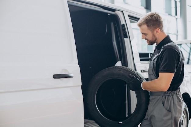 Mecánico de automóviles sosteniendo neumáticos nuevos por la camioneta blanca