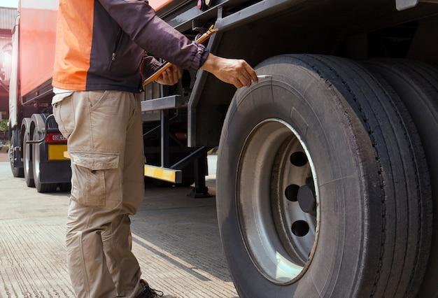 Un mecánico de automóviles sostiene un portapapeles con la inspección de un neumático de camión.