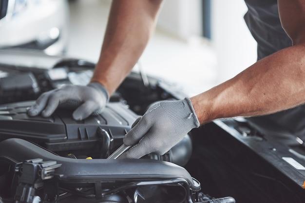 Mecánico de automóviles trabajando en garaje. servicio de reparación.