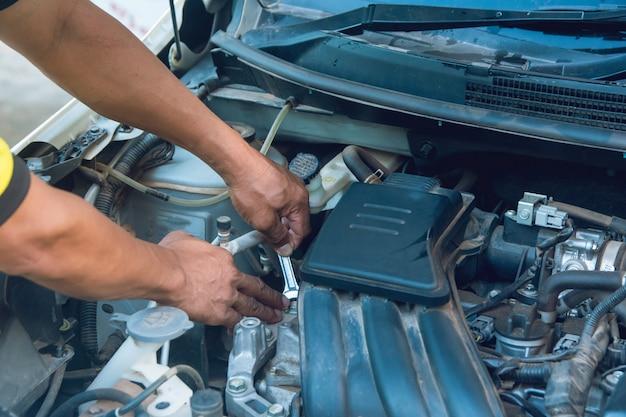 Mecánico de automóviles trabajando con llave en el garaje. servicio de reparación.