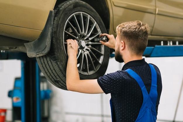 Mecánico de automóviles tratando de establecer el zócalo en la rueda de auto