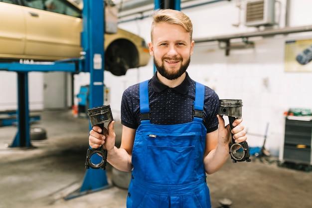 Mecánico de automóviles en uniforme manejo de pistones del motor