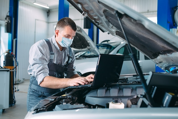 Mecánico de automóviles usando una computadora portátil para diagnosticar y verificar las piezas de los motores de los automóviles para su reparación y reparación