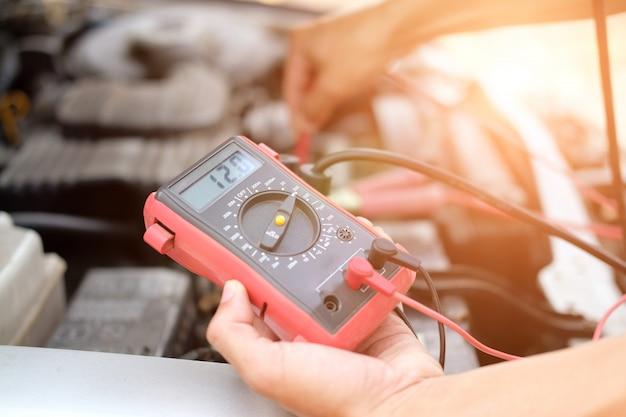 Mecánico de automóviles verifique el voltaje de la batería del automóvil mediante un multímetro voltímetro