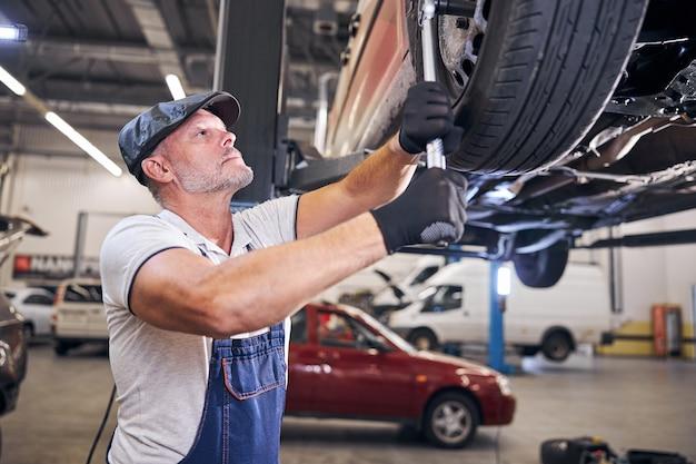Mecánico barbudo que repara la rueda del coche en la estación de servicio automático