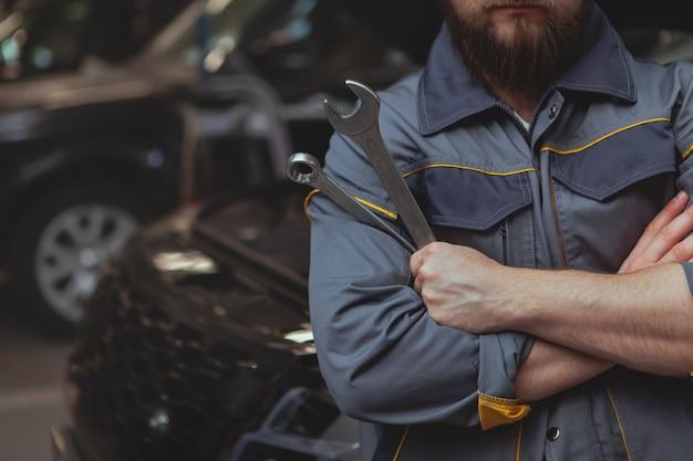 Mecánico barbudo trabajando en la estación de servicio de automóviles