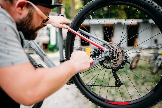 El mecánico de bicicletas ajusta los frenos de disco traseros