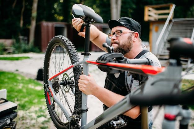 Mecánico de bicicletas ajusta con herramientas asiento de bicicleta