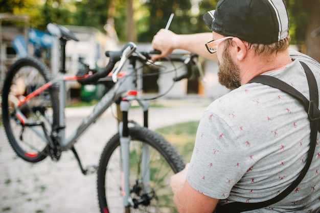 Mecánico de bicicletas en delantal ajusta bicicleta al aire libre