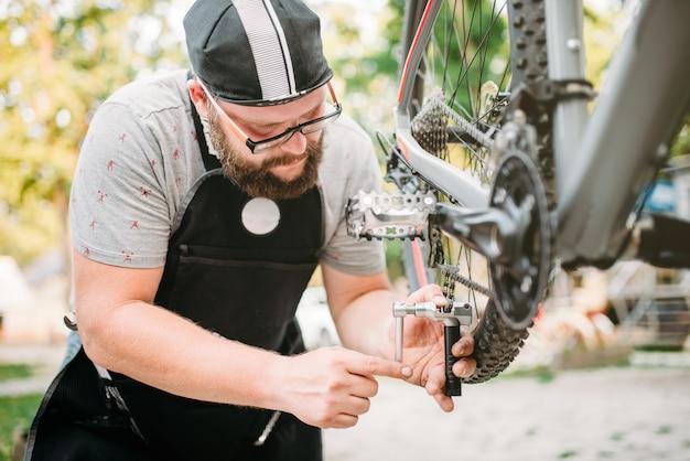 Mecánico de bicicletas en delantal ajusta la cadena de la bicicleta