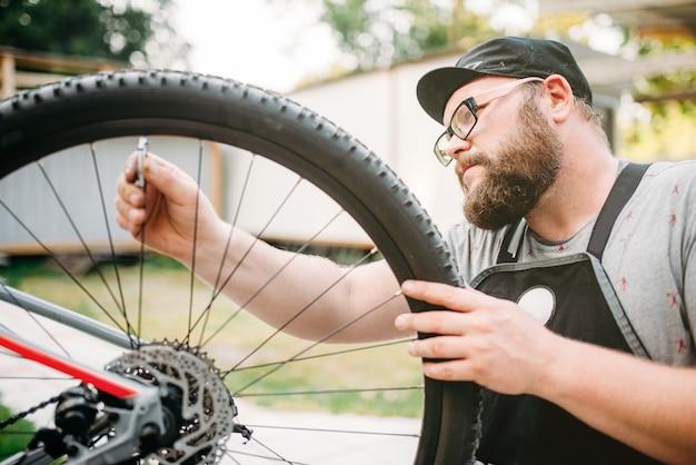 Mecánico de bicicletas en delantal ajusta radios de bicicleta