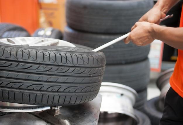 Mecánico cambiando el neumático del coche closeup