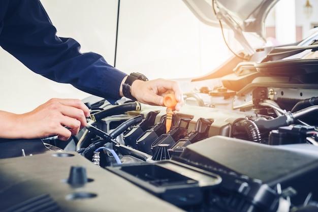 Mecánico cambiante mecánico de aceite en el servicio de reparación de automóviles.