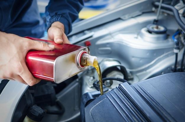 Mecánico de cambiar el aceite del motor en el vehículo automóvil