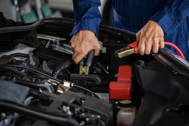 Mecánico de carga manual de la batería del automóvil con electricidad a través de cables de puente