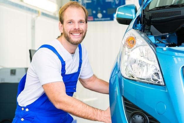Mecanico de coches y auto en taller de servicio.