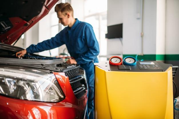 El mecánico comprueba el sistema de aire acondicionado en el coche