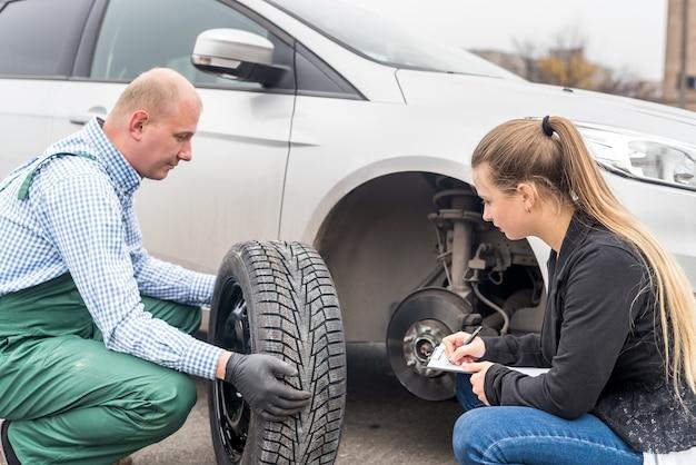 Mecánico y conductor mirando rueda de repuesto