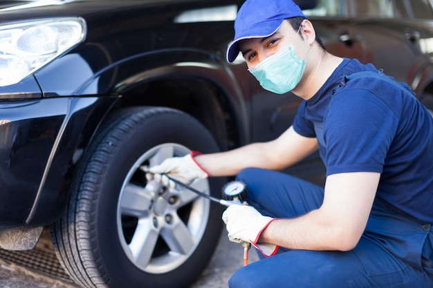 Mecánico enmascarado inflando un neumático