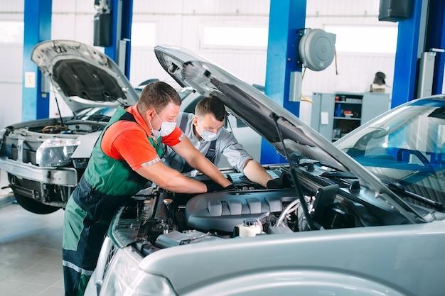Un mecánico enmascarado revisa el automóvil en la estación de servicio.
