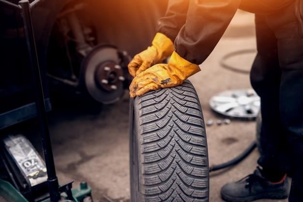 Mecánico experimentado con guantes naranjas apoyado en un neumático al lado del automóvil sin ruedas.