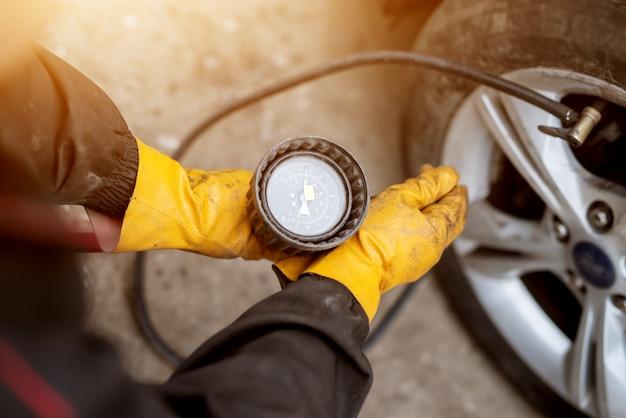 Un mecánico experimentado con guantes naranjas está llenando aire con precisión y ajustando su presión en la rueda de un automóvil.