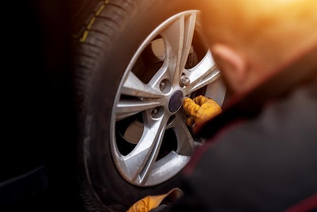 Un mecánico experimentado con guantes naranjas está poniendo tornillos en una rueda colocada en un automóvil.