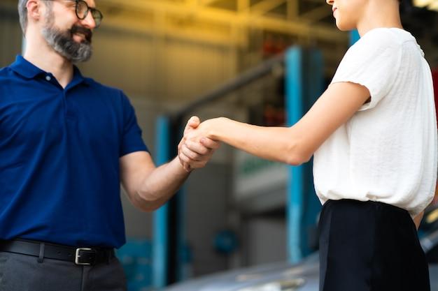 Mecánico experto estrechar la mano del cliente satisfecho y trabajar en el garaje de la estación de mantenimiento de reparación de automóviles. satisfacción en el servicio.