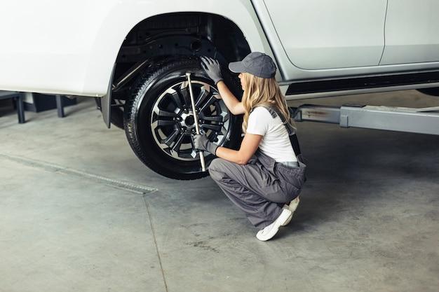 Mecánico femenino de alto ángulo que cambia las ruedas del coche