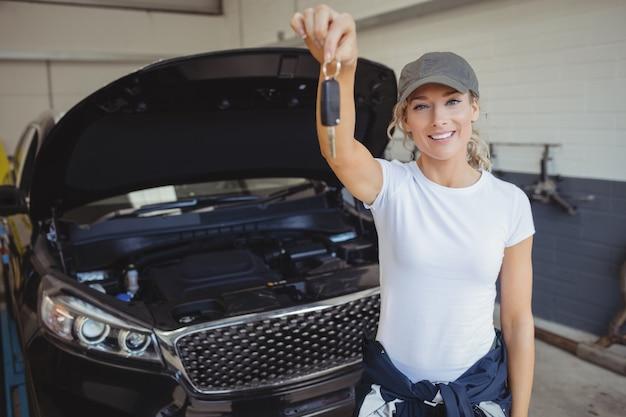 Mecánico femenino en garaje sosteniendo la llave del coche