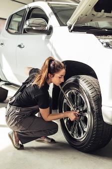 Mecánico femenino que fija las ruedas del coche