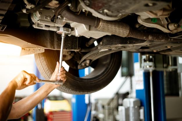 Mecánico está girando la tuerca para arreglar el coche en el garaje, servicio de reparación.