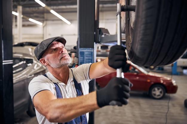 Mecánico guapo reparar rueda de coche en la estación de servicio automático