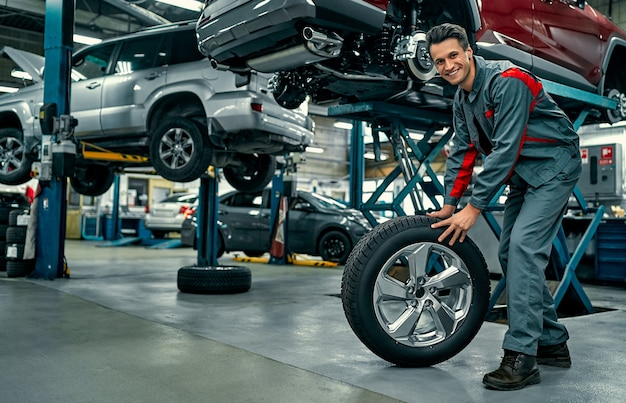 Mecánico guapo en uniforme está trabajando en auto servicio. reparación y mantenimiento de automóviles. sosteniendo la rueda del coche.