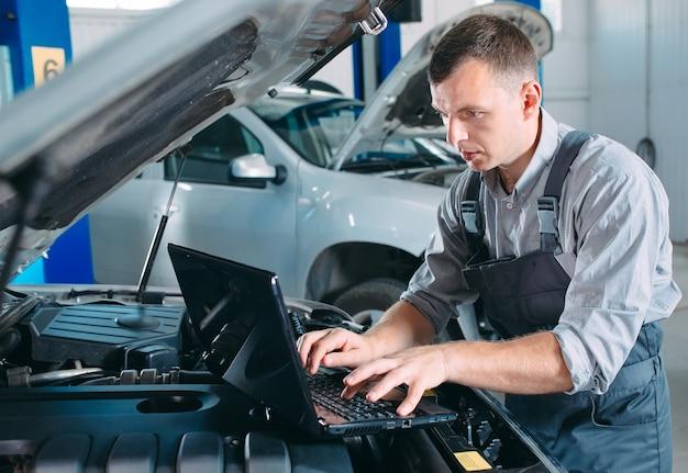 Mecánico guapo en uniforme trabajando en auto servicio