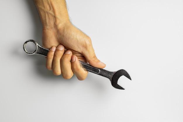 Mecánico con una herramienta llave en mano.