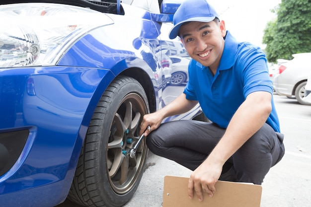 Mecánico hombre sosteniendo portapapeles y comprobar el coche