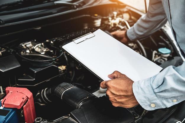 Mecánico manual usando la lista de verificación para volver a verificar después de cambiar la pieza de repuesto.