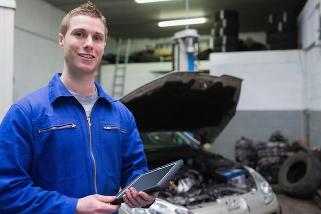 Mecánico masculino con tableta digital en el garaje