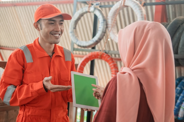 Un mecánico masculino en un wearpack vistiendo una tableta digital con una clienta vistiendo hijab contra una rejilla para neumáticos